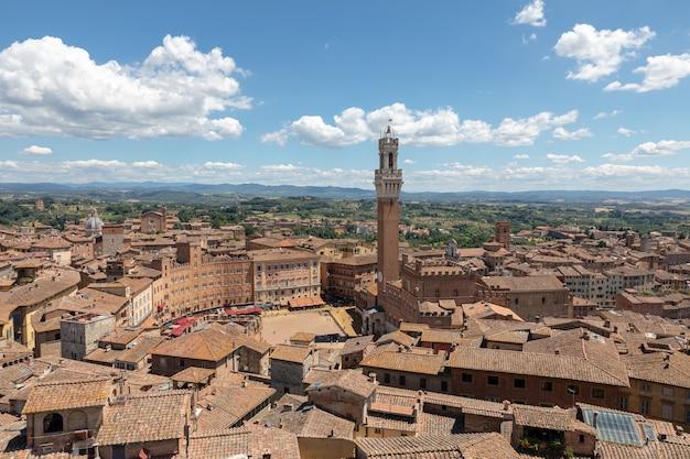Панорамный вид на город сиена с площади пьяцца-дель-кампо и торре-дель-манджа - это башня в городе из сиенского собора (duomo di siena). летний солнечный день и драматическое голубое небо