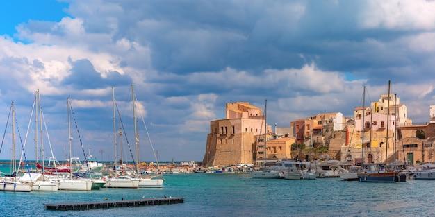イタリア、シチリア島、沿岸都市カステッランマーレデルゴルフォの港、カラマリーナの日当たりの良い中世の要塞のパノラマビュー
