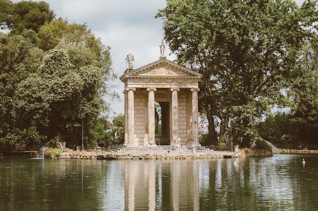 빌라 보르게세(villa borghese)의 공공 공원에 있는 아스클레피우스 신전(tempio di esculapio)과 호수의 탁 트인 전망. 여름날과 푸른 하늘