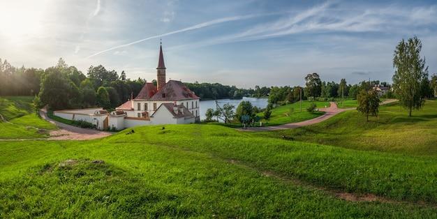 Панорамный вид на красивый природный ландшафт со старым белым замком в солнечный летний день. гатчина. россия.