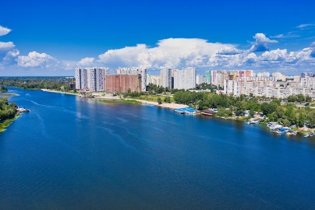 Панорамный вид на левый берег реки днепр в киеве днем на фоне голубого неба и русла реки