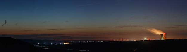 Панорамный вид на долину реки с атомной электростанцией. пейзаж после заката, сумеречное небо.