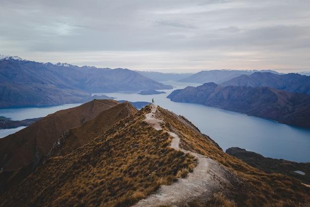 가벼운 cloudscape 아래 거리에있는 산들과 뉴질랜드의 roys peak의 전경