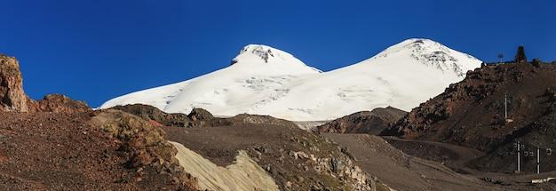 ロシアのコーカサス山脈のエルブルス山の南斜面のパノラマビュー。雪に覆われた山頂と2つの山。