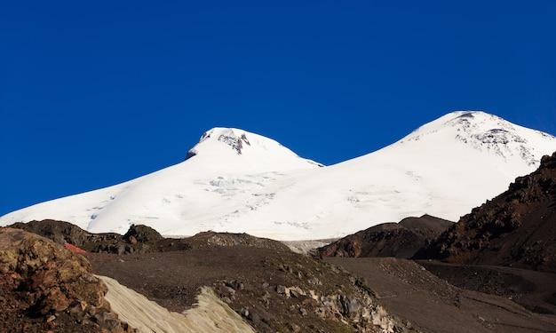 Панорамный вид на южный склон горы эльбрус кавказских гор в россии. заснеженные горные вершины с двумя вершинами.