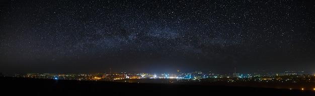 Панорамный вид на звездное ночное небо над городом.