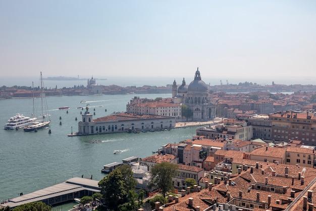 Панорамный вид на венецию и базилику санта-мария-делла-салюте (святая мария здоровья) с кампанилы сан-марко (campanile di san marco). пейзаж летнего дня и солнечного голубого неба