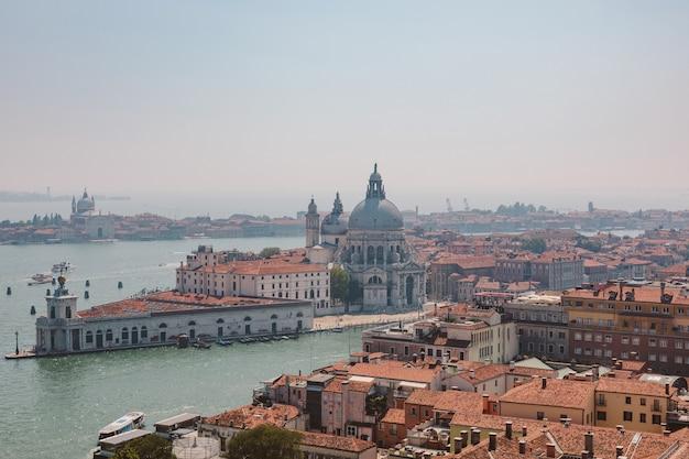 산 마르코 종탑(campanile Di San Marco)에서 베니스(venice) 시와 멀리 산타 마리아 델라 살루트(basilica Di Santa Maria Della Salute)(힐트의 성모 마리아)의 탁 트인 전망. 여름날과 맑은 푸른 하늘의 풍경 프리미엄 사진