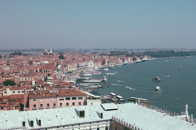 サンマルコ鐘楼からの歴史的建造物と海岸のあるヴェネツィア市のパノラマビュー。夏の日の風景と晴れた青空