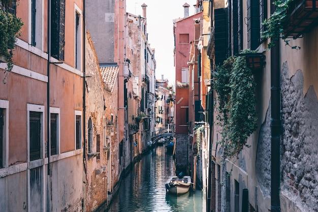 Панорамный вид на узкий канал венеции с историческими зданиями и лодкой с моста. пейзаж летнего солнечного дня