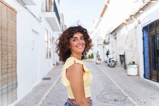 スペインの休日の女性のパノラマビュー。白いスペインの海岸の概念。旅行中の幸せな女性。