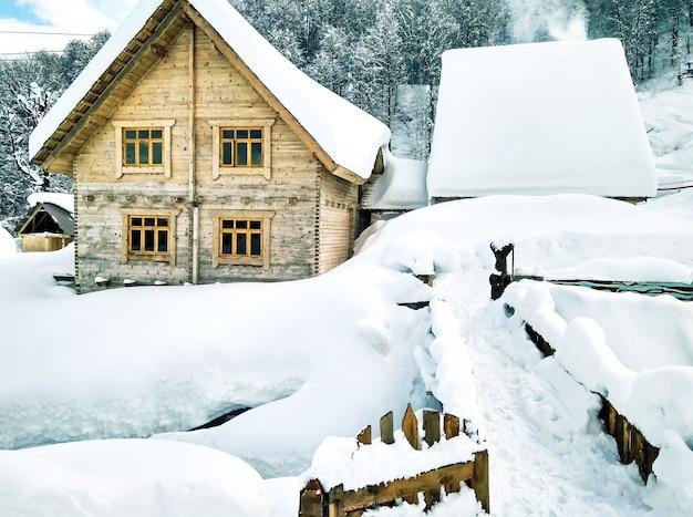 눈 덮인 목조 주택과 다리의 탁 트인 전망. 겨울 풍경입니다. 시골 배경