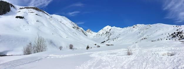 青い空の下で冬に雪に覆われたフランスアルプスの山のパノラマビュー