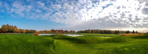 池と秋の公園の緑の牧草地のパノラマビュー。 10月の森と湖、晴れた日の自然風景