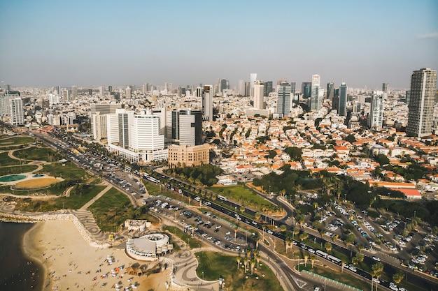 Панорамный вид на крыши тель-авива, израиль. современные здания и песчаный пляж тель-авива на фоне неба. городская жизнь, мегаполис в израиле. skycrapers, южный портовый город