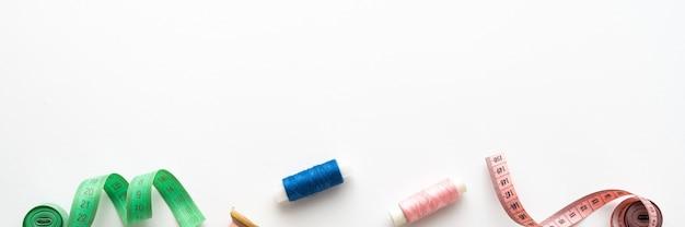 흰색 배경에 실, 가위, 단추, 핀 및 기타 재봉 액세서리가 있는 재봉 구성에 대한 탁 트인 전망. 긴 배너, 위쪽 보기, 복사 공간, 평평한 위치, 조롱. 텍스트를 위한 공백