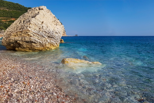 Panoramic view of pebble beach with clear azure water and layered rocks