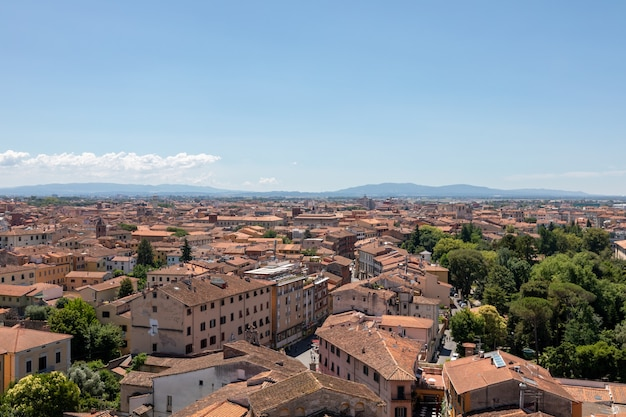 Panoramic view of pisa city with historic buildings and far away mountains from tower of pisa. summer day and sunny blue sky