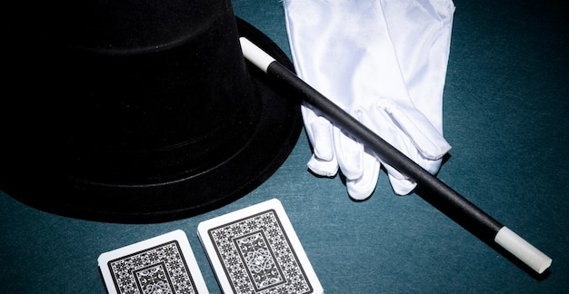 Panoramic view of playing card; white gloves; top hat and magic wand on green background