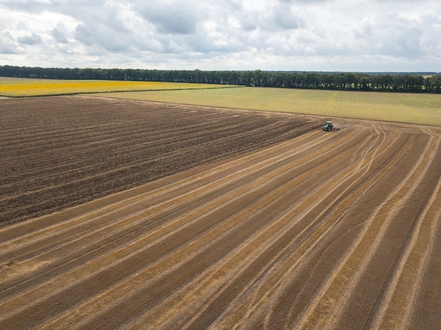 Panoramic view of plowing the ground after harvesting on the field in the autumn time. aerial view from the drone of the field after harvest