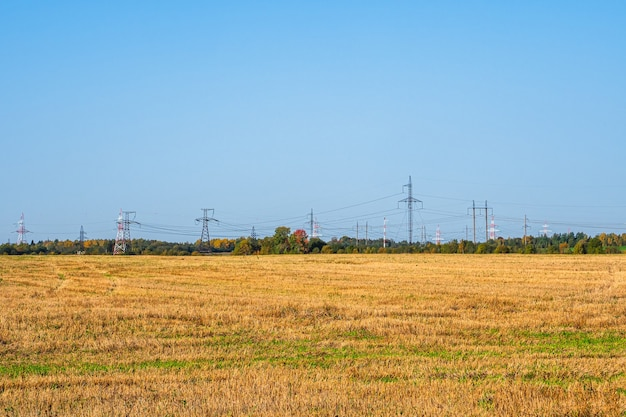 Panoramic view of the power line and cell towers standing in a row on the horizon in the autumn field