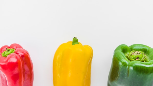 Panoramic view of red; yellow and green bell peppers on white surface