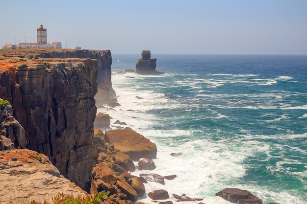 Panoramic view of rock sea shore with waves and lighthouse in sunny day.seaside town peniche,portugal.