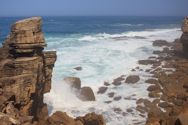 Panoramic view of sea rock shore with waves in sunny day.seaside town peniche,portugal.