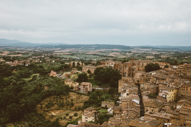 Panoramic view of siena city with historic buildings and far away green fields from torre del mangia is a tower in city. summer sunny day and dramatic blue sky