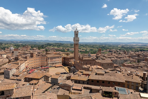 Panoramic view of siena city with piazza del campo and the torre del mangia is a tower in city from siena cathedral (duomo di siena). summer sunny day and dramatic blue sky