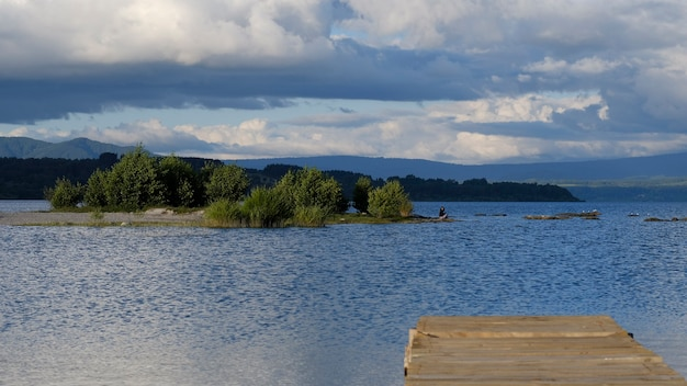 Panoramic view of a small island where a person is out of focus seen from a wooden dock.