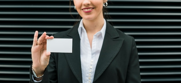 Panoramic view of smiling businesswoman showing blank business card standing against stripe backdrop