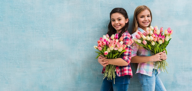 Panoramic view of smiling two girls holding pink and yellow tulips bouquet in hands