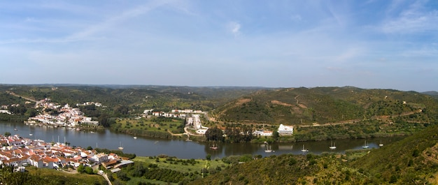 Panoramic view of spanish sanlucar and portuguese alcoutim towns divided by the guadiana river.