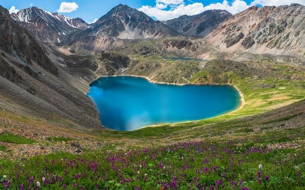 ハートの形をした山の湖のパノラマビュー。高山の花の谷に湖のある雰囲気のある緑の風景。高原グレンの山の湖との素晴らしい景色。