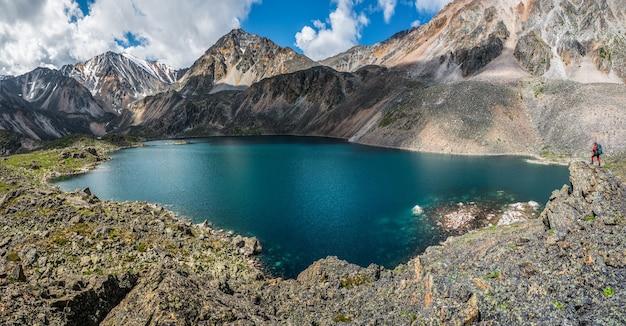 山々を背景に山の湖のパノラマビュー。高山の谷に湖のある雰囲気のある緑の風景。高原グレンの山の湖との素晴らしい風景