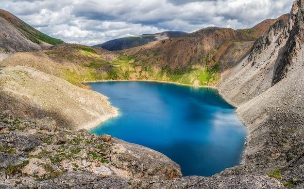 山々を背景に山の湖のパノラマビュー。高山の谷に湖のある雰囲気のある緑の風景。高原グレンの山の湖との素晴らしい景色