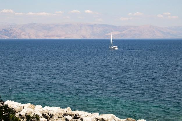 Панорамный вид на море и небольшую яхту в солнечный день. корфу. греция.