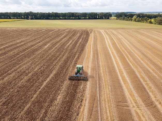Panoramic view of tractor plowing the soil after harvesting on the field. aerial view from the drone of the field after harvest
