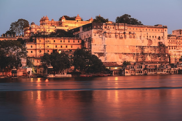 Panoramic view of the udaipur city palace complex at night from lake pichola in rajasthan, india