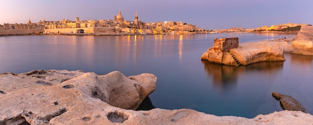 Panoramic view of valletta skyline with churches of our lady of mount carmel and st. paul's anglican pro-cathedral at sunset as seen from sliema, valletta, capital city of malta