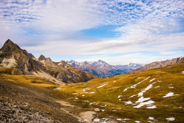 Panoramic view of valley and mountain range in a colorful autumn with yellow meadows and high mountain peaks.