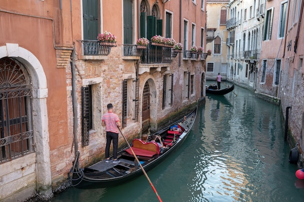 Panoramic view of venice canal with historical buildings and gondolas from bridge. landscape of summer evening day