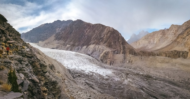 Panoramic view of white passu glacier and glacial moraine, surrounded by mountains in karakoram range.