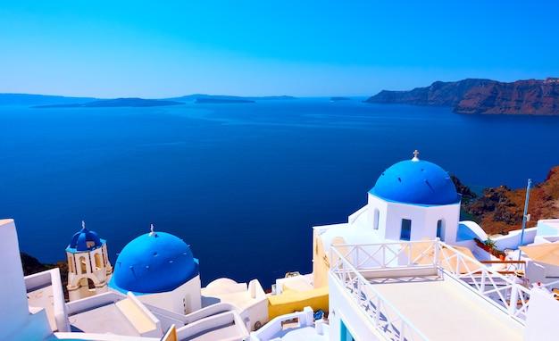 그리스 산토리니 섬의 이아 마을에 파란색 돔이 있는 그리스 정교회의 탁 트인 전망