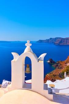 그리스 산토리니 섬의 이아에 있는 작은 종탑이 있는 그리스 정교회의 탁 트인 전망. 텍스트를 위한 공간