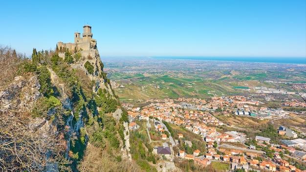 바위 기슭에 있는 산 마리노(san marino)의 첫 번째 탑과 보르고 마조레(borgo maggiore)가 있는 탁 트인 전망 - 풍경