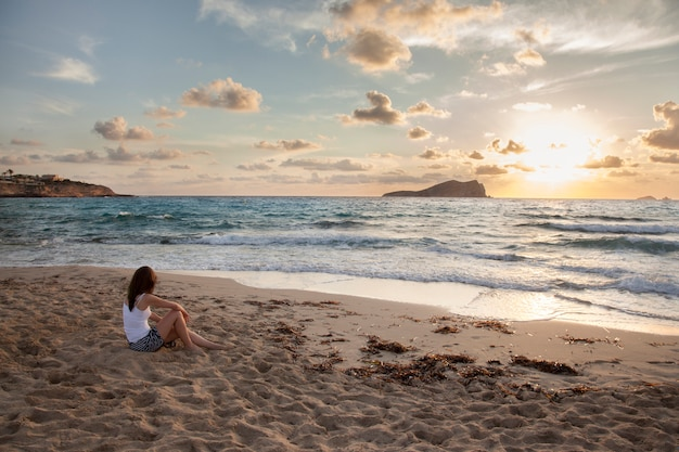 Panoramic view of a woman on a sunset beach in ibiza