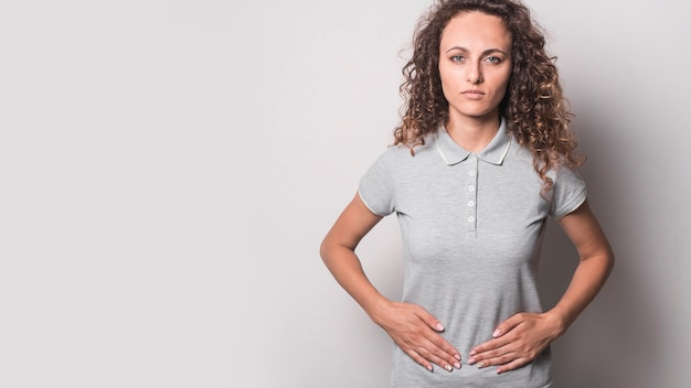 Panoramic view of young woman having stomach ache against gray background