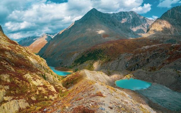 ラズライト湖のある雑多な山の谷のパノラマビュー。色とりどりのとがった岩のある風光明媚な山の風景。鋭い岩と色とりどりの山の谷のあるカラフルな高原の風景。